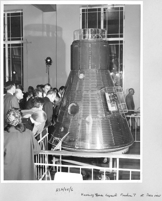 Black and white photograph of a press viewing of the Freedom 7 space capsule, 1965