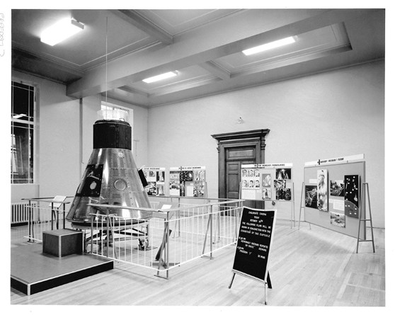 Black and white photograph of the Display of Space Conquest exhibition at the Science Museum, London, 1965, showing the easel displayed next to the capsule