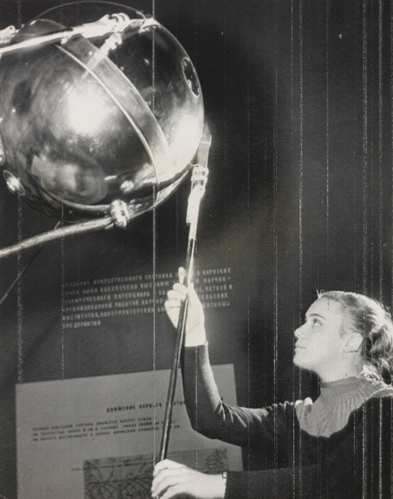 Black and white photograph of a girl touching the antenna of the Sputnik satellite