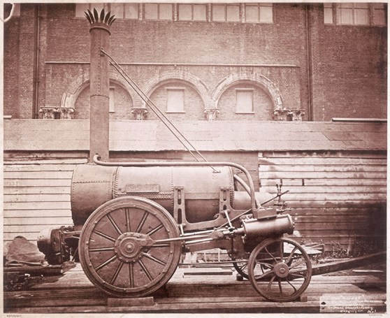 Sepia photograph of the Rocket steam powered rail engine outside the Patent Office Museum, London, 1876