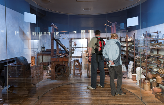 Photograph of Watt's workshop in situ in the new Watt exhibition at the Science Museum, London, showing the curved glass surround that separates the audience from the workshop