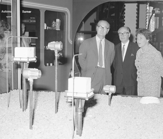 Black and white  photograph showing Margaret Weston, Frank Greenaway and an unknown male guest visiting a display of gas meters