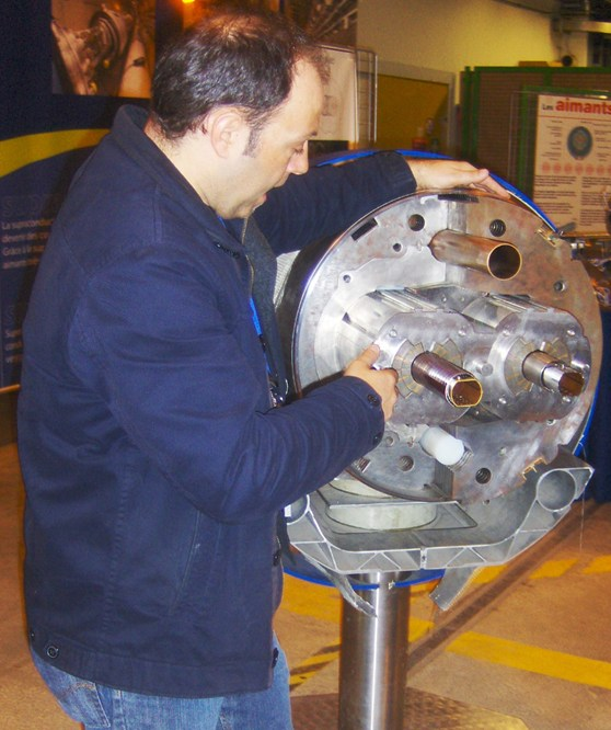 A CERN magnet engineer talks as points out features on a cross section of a circular super-conducting magnet