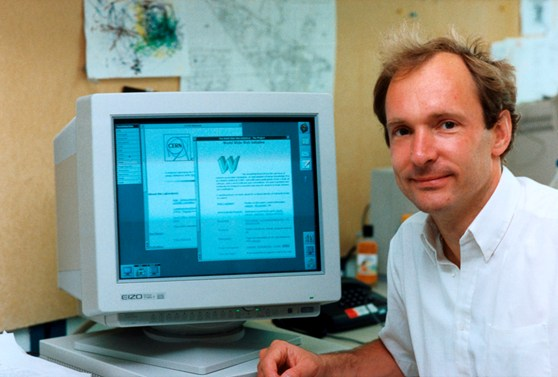 Photograph of Tim Berners-Lee sitting next to a computer display on which the words world wide web initiative are legible as well as an old CERN logo