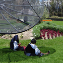 Two female ecuadorians sit in the shade beneath a large satellite dish