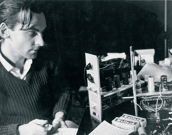 Black and white photograph of engineer Graham Wrench writing notes as he works on constructing part of the Oramics Machine