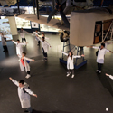 Several members of the National Youth Theatre stand with arms outstretched in the Flight Gallery at the Science Museum