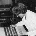 Black and white photograph of Daphne Oram leaning over the Oramics Machine and drawing black lines on one of the acetate strips