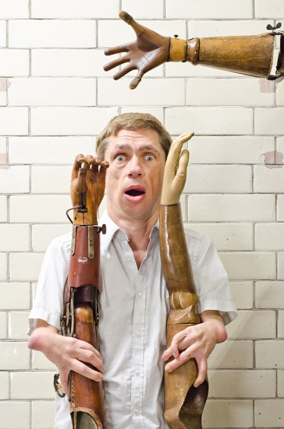 Colour photograph of Mat Fraser holding up two historical wooden prosthetic arms