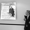 Black and white photograph of Mat Fraser alongside an old German poster depicting a doctor and a disabled character