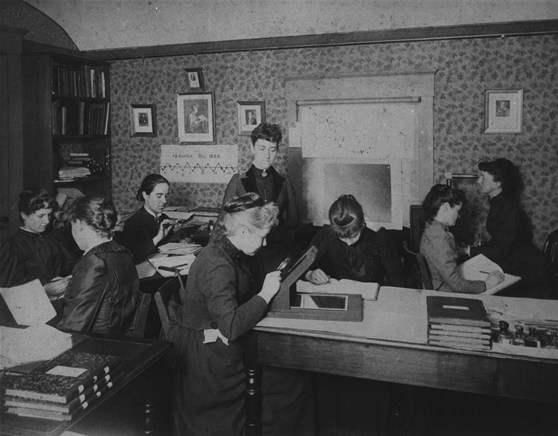 Black and white photograph from the 1880s of 8 women attempting to classify stars from recorded observations