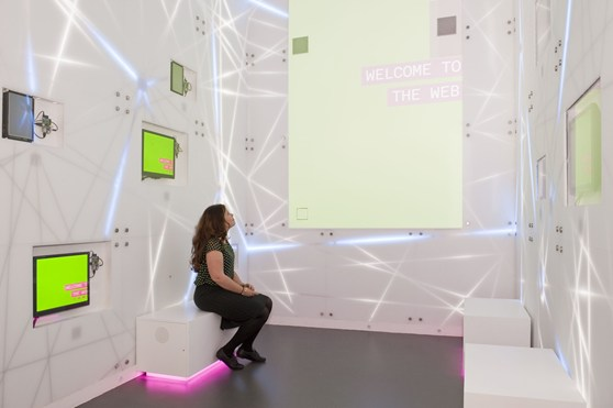 Colour photograph of the inside of a colourful and brightly lit installation in the Information Age exhibition showing a woman looking at a large screen with the text welcome to the web