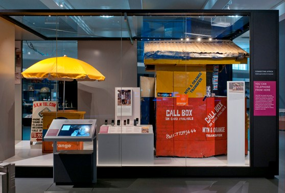 Colour photograph of the connecting Africa display in Information Age showing a mobile phone repair hut from Cameroon