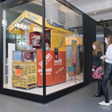 Colour photograph of the connecting Africa display in Information Age showing visitors viewing a mobile phone repair hut from Cameroon