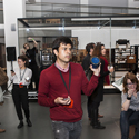 Colour photograph of a number of people taking part in the set up of a live performance in the Information Age gallery