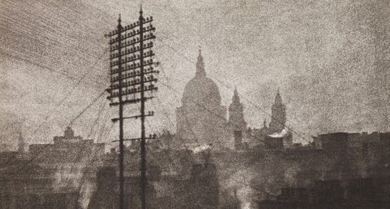 Grainy sepia photograph of a tall telegraph pylon in front of the distant silhouette of Saint Pauls Cathedral