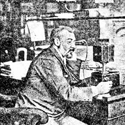 Black and white printed photograph of a man sitting at a desk holding an early table telephone from 1891