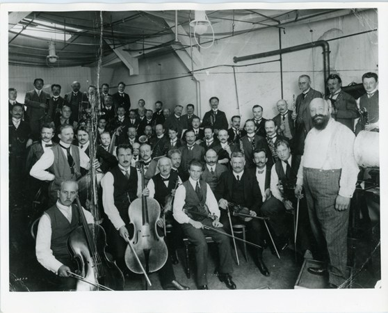Black and white photograph of the Berlin Philharmonic Orchestra with their instruments in a Gramophone recording studio