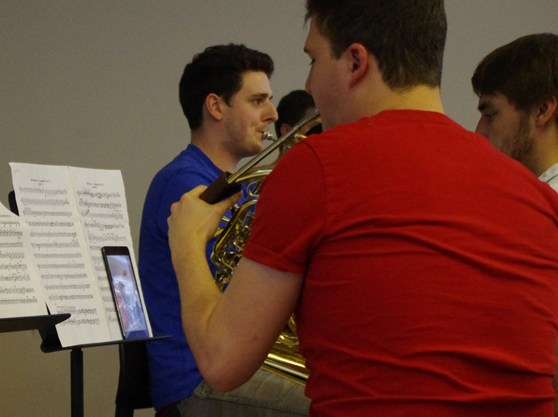 Colour photograph of a member of RCM playing the french horn with the conducting being done via a tablet computer