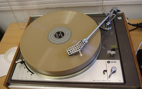 Colour photograph of a freshly recorded wax disc playing on a transcription turntable