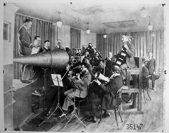 Black and white photograph of a studio orchestra playing into a megaphone shaped recording instrument