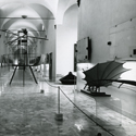 Black and white photograph of a corridor in which is displayed a number of leonardo models paintings and information plaques