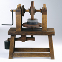 Colour photograph of a working wooden model of a machine for grinding concave mirrors