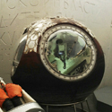 Colour photograph of an early soviet spacesuit next to a spherical descent module