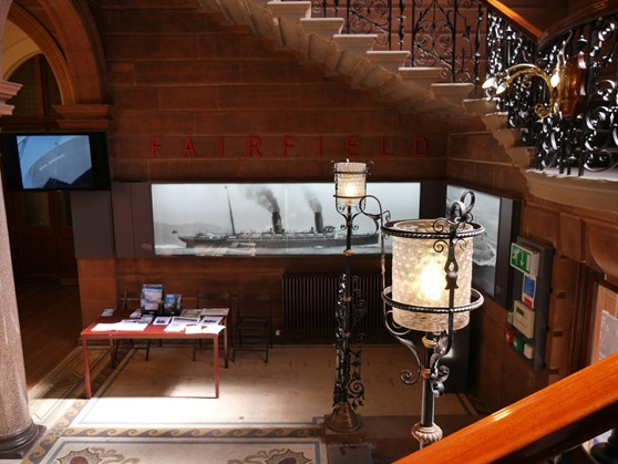 Colour photograph of the entrance chamber of Fairfield showing staircase, stone archways and a large black and white photograph of a ship