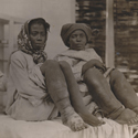 Black and white photograph of two adult females showing elephantiasis of the legs accompanied by a nun