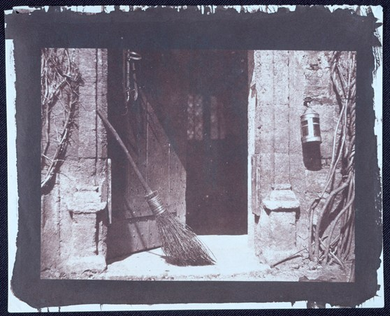 Early black and white photograph by William Henry Fox Talbot of an open door with broom and lantern