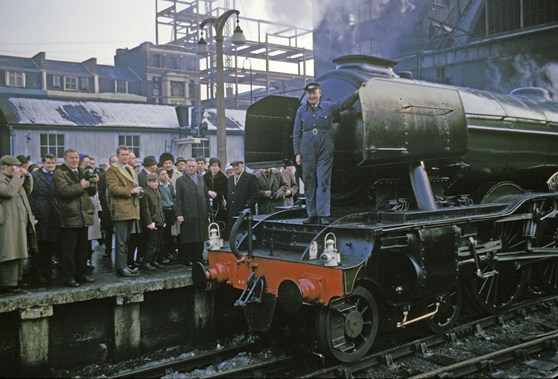 Colour photograph of the Flying Scotsman steam train on track at London Kings Cross station with the restorer Alan Spegler standing on the front