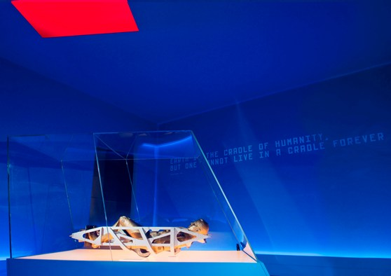 Colour photograph of a section of the Cosmonauts exhibition showing a mannequin lying inside a spacecraft seat
