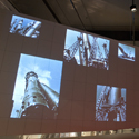 Colour photograph of a section of the Cosmonauts exhibition showing a section of a rocket with images of the rocket projected onto the wall