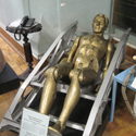 Colour photograph of a gold coloured mannequin lying inside a space craft pilot seat