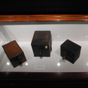 Colour photograph of four early wooden box cameras on display in a glass case
