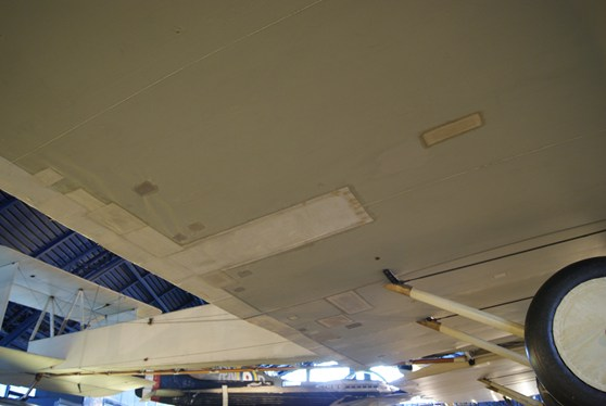 Colour photograph of the underside of the Vickers Vimy aircraft showing numerous patches applied during conservation