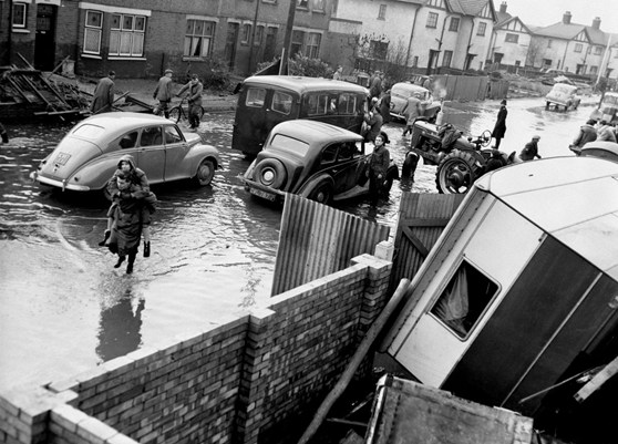 Black and white photograph of a flooded residential street in mid twentieth century