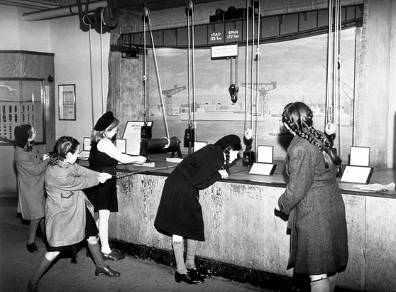 Black and white photograph of schoolgirls lifting weights using pulleys at a museum exhibition