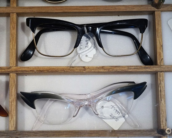 Colour photograph of a pair of mens black NHS spectacles and a pair of womens NHS cats eye spectacles