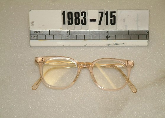 Colour photograph of a pair flesh coloured NHS spectacles