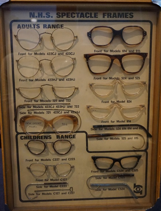 Colour photograph of a 1970s display case showing various styles of NHS spectacles
