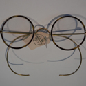 Colour photograph of a pair of Windsor style NHS spectacles with Xylonite covered rims