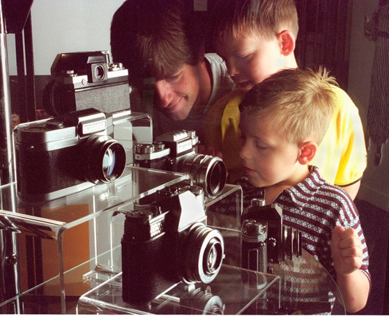 Colour photograph of a father and two children looking at Kodak cameras at the National Museum of Photography Film and Television