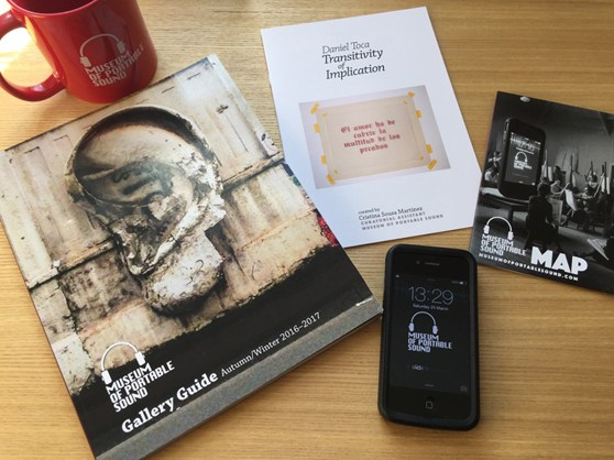Colour photograph of Museum of Portable Sound visitor materials including a mug, gallery guide, phone app, map and brochure