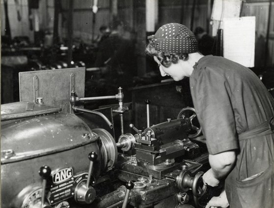 Black and white photograph of a woman working a machine tool during the mid twentieth century