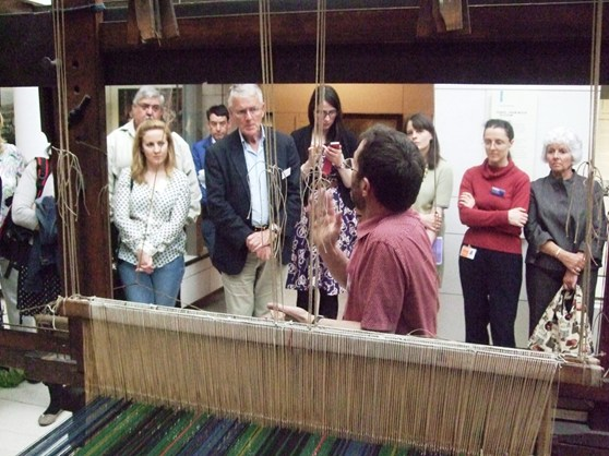 Colour photograph of of a weaver demonstrating how to work a loom in front of a museum audience