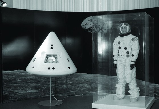Black and white photograph of an exhibition display containing a spacewalk suit and a reentry module