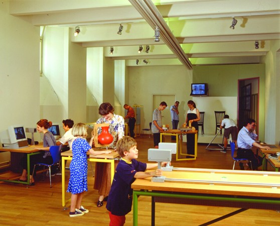 Colour photograph of museum goers using experimentation devices within a museum exhibition
