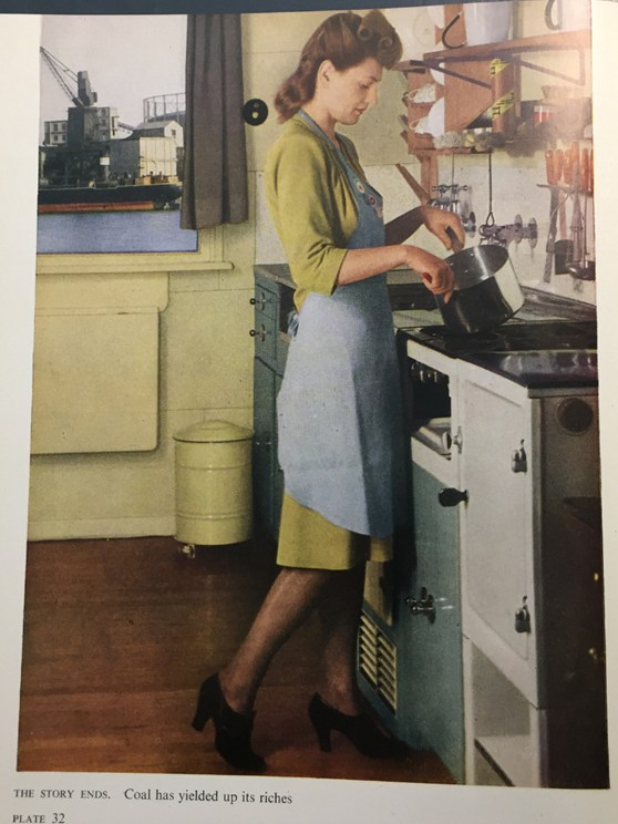 Page in a magazine showing a colour photograph of a woman cooking over a stove. The caption reads coal has yielded up its riches